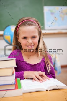 Portrait of young schoolgirl reading a book
