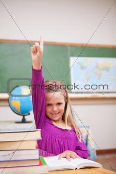 Portrait of young schoolgirl raising her hand