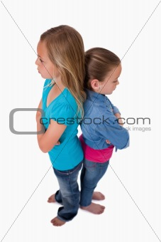 Portrait of two girls standing back to back