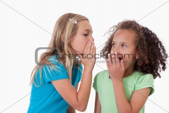 Cute girl whispering a secret to her friend
