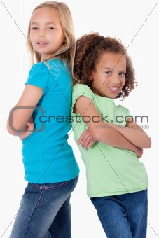 Portrait of happy girls standing back to back