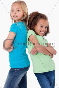 Portrait of smiling girls standing back to back