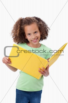 Portrait of a smiling girl reading a fairy tale