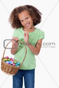 Portrait of a cute girl holding a basket full of Easter eggs