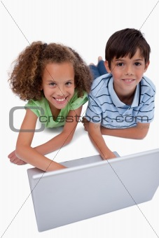Portrait of children using a notebook while lying on the floor