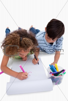 Portrait of children drawing while lying on the floor