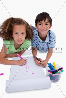Portrait of cute friends drawing while lying on the floor