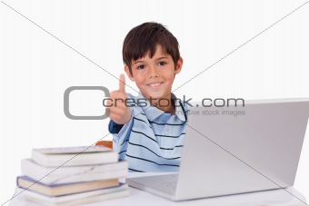 Boy using a notebook with the thumb up