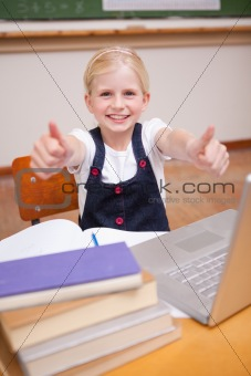 Portrait of a girl using a notebook with the thumbs up