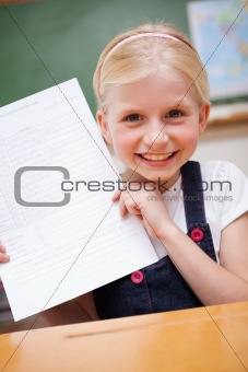 Portrait of a happy girl showing her school report