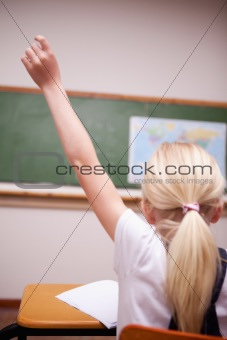 back view of a schoolgirl raising her hand