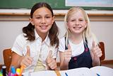 Portrait of happy pupils working together with the thumbs up