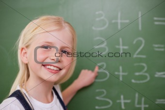 Blonde schoolgirl pointing at something
