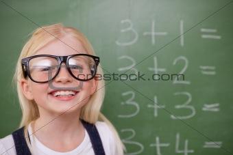 Smart schoolgirl posing in front of a blackboard