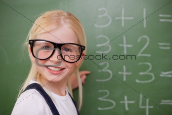 Smiling smart schoolgirl pointing at something