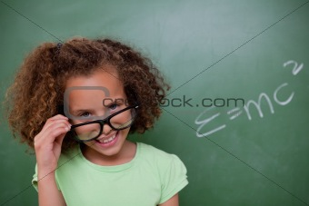 Smart schoolgirl looking above her glasses