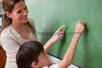 Schoolteacher helping a schoolboy doing an addition