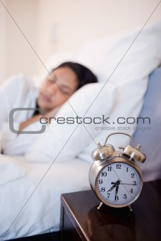Alarm clock next to bed in which woman is sleeping