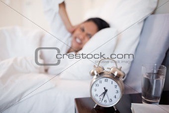 Alarm clock making woman cover her ears