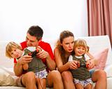 Family spending time together and playing on console at home