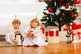 Two twins girl sitting with presents near Christmas tree