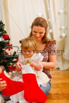 Mom looking with daughter inside of Christmas socks near Christmas tree