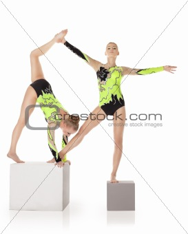 Two high skill acrobats stand on cube