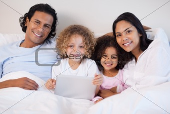 Family together on the bed with laptop