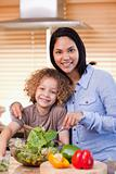 Mother and daughter preparing salad in the kitchen together