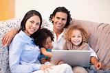 Family using laptop on the sofa together