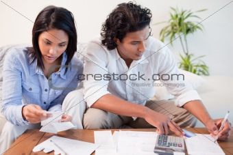 Couple checking bills in the living room