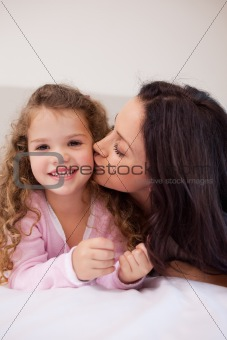 Mother giving her little daughter a kiss