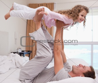 Father playing plane with his daughter