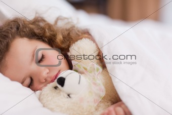 Girl sleeping with her teddy