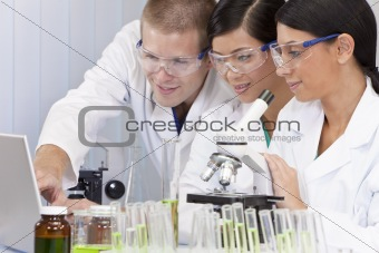 Interracial Team of Scientists In Laboratory With Laptop