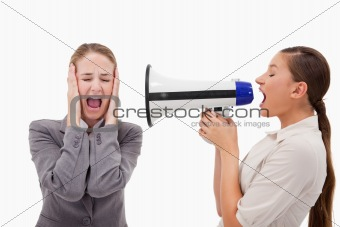 Young manager yelling at her employee through a megaphone