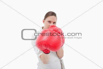 Young businesswoman boxing