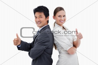 Business people standing back to back with the thumb up