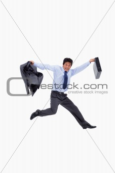 Cheerful businessman jumping while holding his jacket and a briefcase