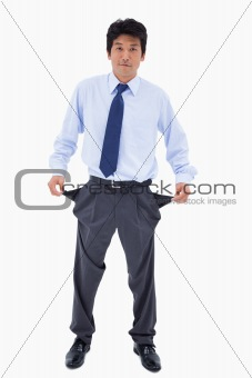 Portrait of a businessman showing his empty pockets