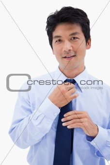 Portrait of a smiling businessman fixing his tie