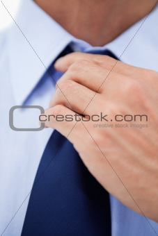 Close up of a businessman fixing his tie