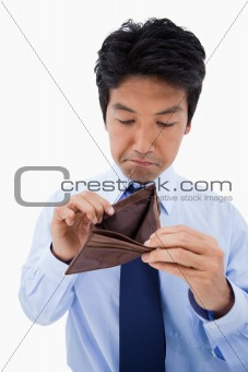 Portrait of a sad businessman showing his empty wallet