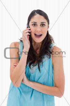 Portrait of an amazed woman making a phone call