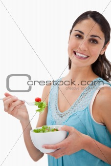Portrait of a young woman eating a salad