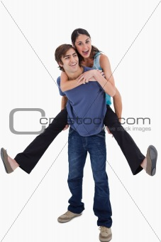Portrait of man holding his girlfriend on his back