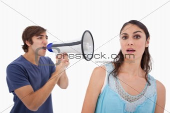 Man yelling at her girlfriend through a megaphone