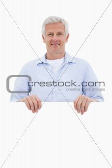 Portrait of a mature man standing behind blank board