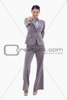 Portrait of a young brunette businesswoman pointing at the viewer