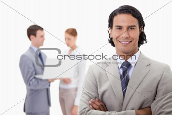 Smiling businessman with colleagues working on laptop behind him